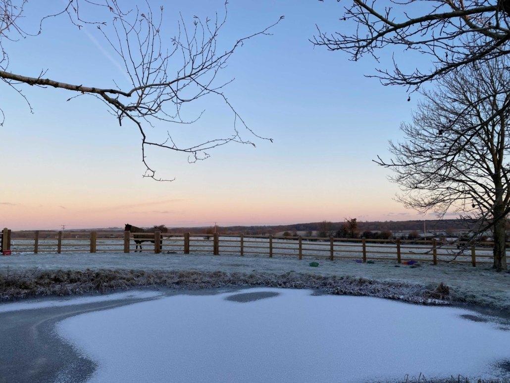 Icy frozen winter pond at Hall Farm Dadlington